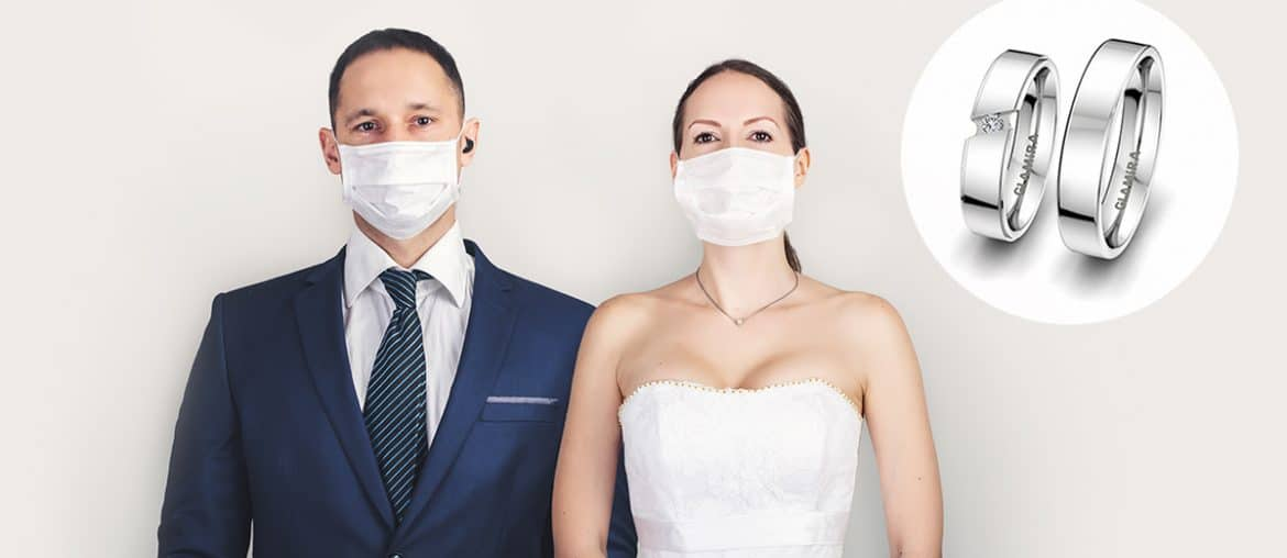 married couple with masks standing next to rings